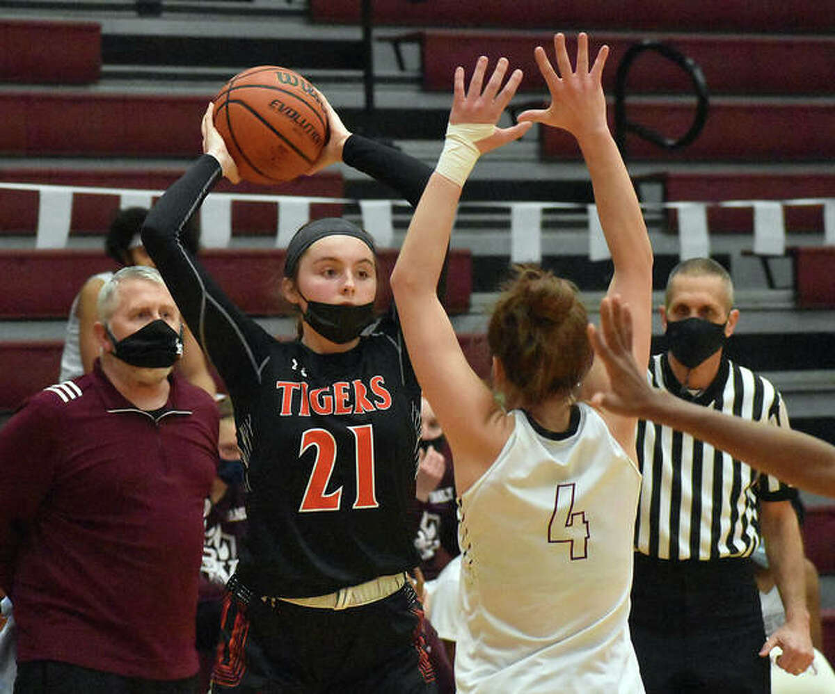 Edwardsville junior Elle Evans looks for an open teammate while being guarded by Belleville West's Reese Bennett.