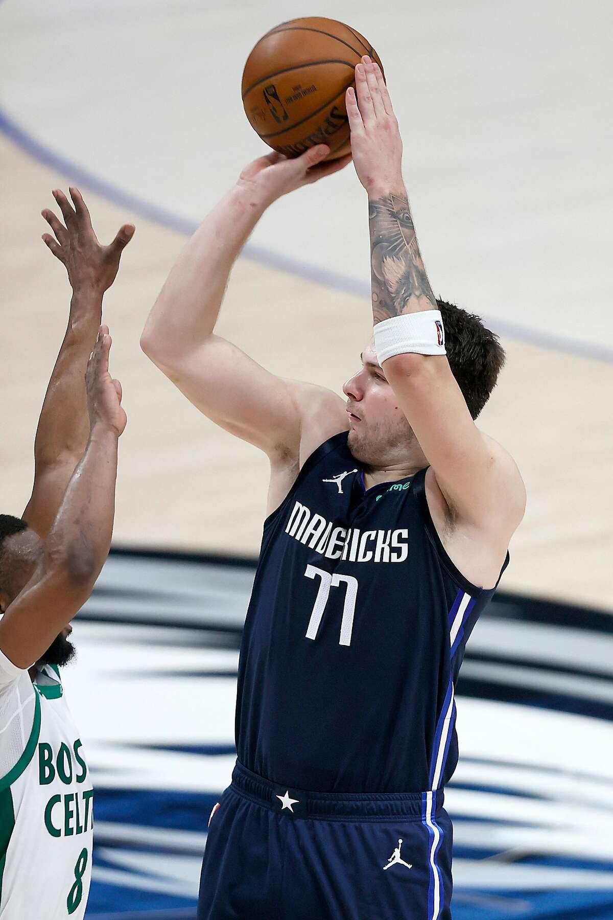 Mavericks guard Luka Doncic hits the game-winning 3-pointer over the Celtics' Kemba Walker in Dallas' 110-107 victory.