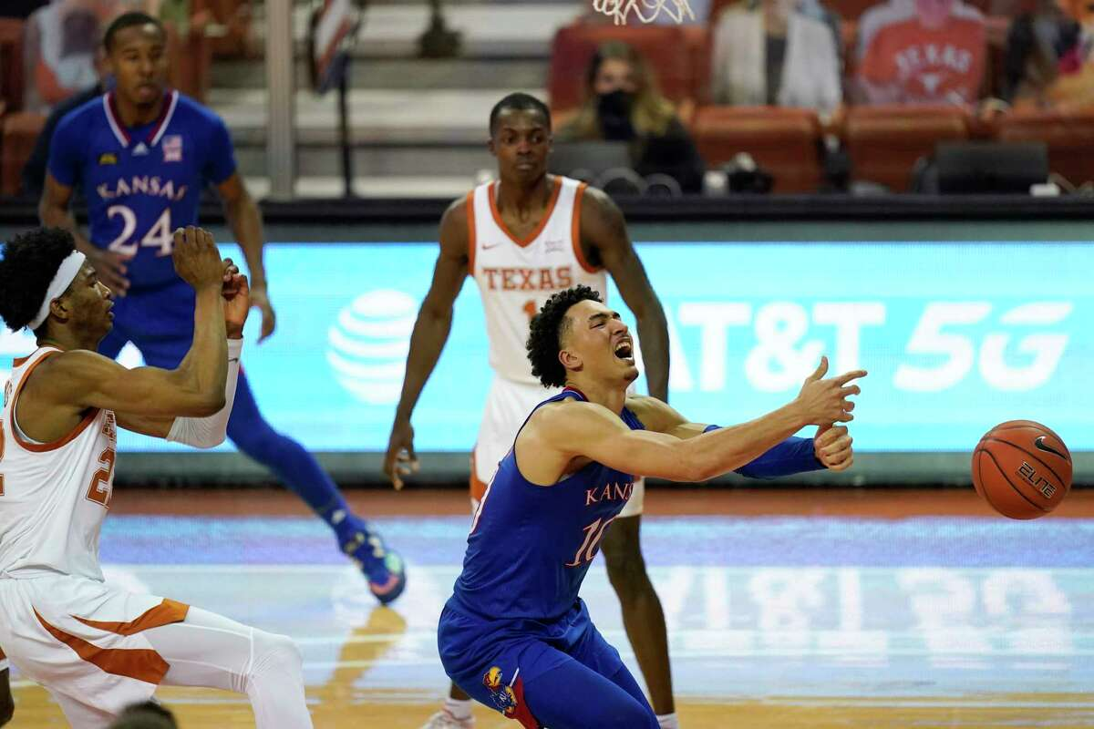 Kansas forward Jalen Wilson loses the ball out of bounds in front of Texas forward Kai Jones, left, while driving to the basket during overtime in an NCAA college basketball game, Tuesday, Feb. 23, 2021, in Austin, Texas. Texas won 75-72. (AP Photo/Eric Gay)