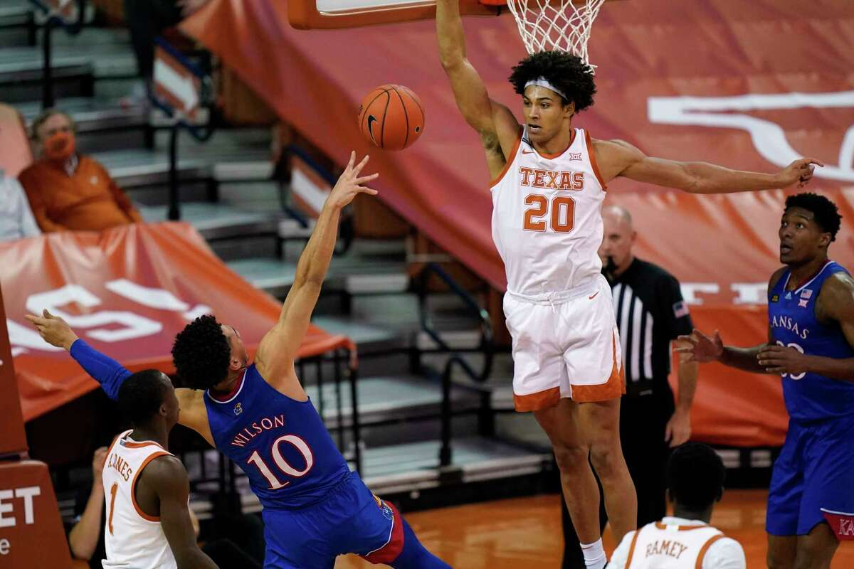 Texas forward Jericho Sims (20) tries to block a shot by Kansas forward Jalen Wilson (10) during the first half of an NCAA college basketball game, Tuesday, Feb. 23, 2021, in Austin, Texas. (AP Photo/Eric Gay)