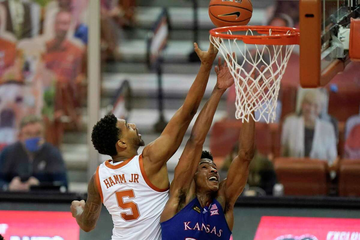 Kansas guard Ochai Agbaji fights for a rebound with Texas forward Royce Hamm Jr. (5) during the first half of an NCAA college basketball game, Tuesday, Feb. 23, 2021, in Austin, Texas. (AP Photo/Eric Gay)