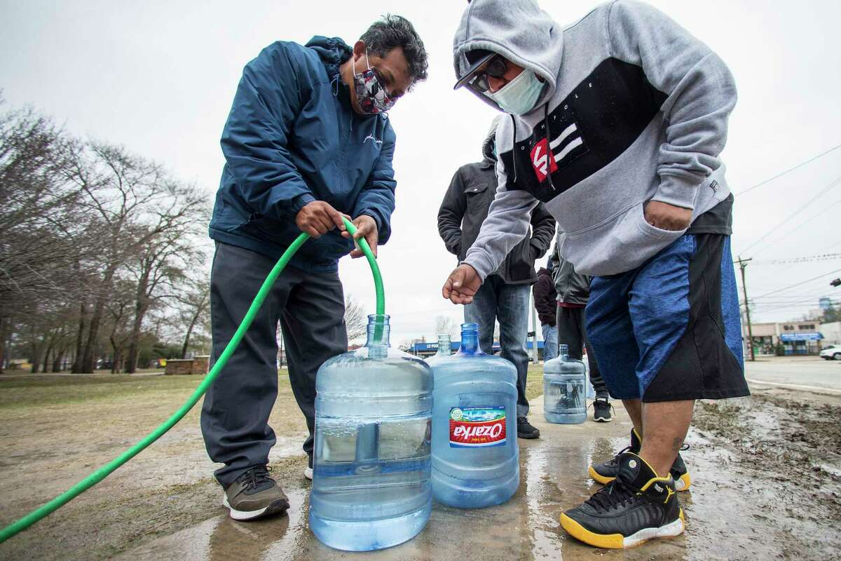Victor Hernandez, left, and Luis Martinez fill their water containers with a hose from a spigot in Haden Park, Thursday, Feb. 18, 2021 in Houston. Texas officials have ordered 7 million people to boil tap water before drinking it following days of record low temperatures that damaged infrastructure and froze pipes. (Brett Coomer/Houston Chronicle via AP)