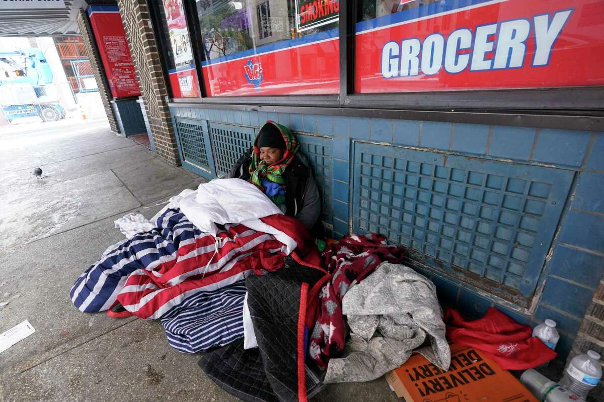 A woman who calls herself Princess uses blankets to keep warm in sub-freezing temperature as she sits outside of a business, Tuesday, Feb. 16, 2021, in San Antonio. (AP Photo/Eric Gay)