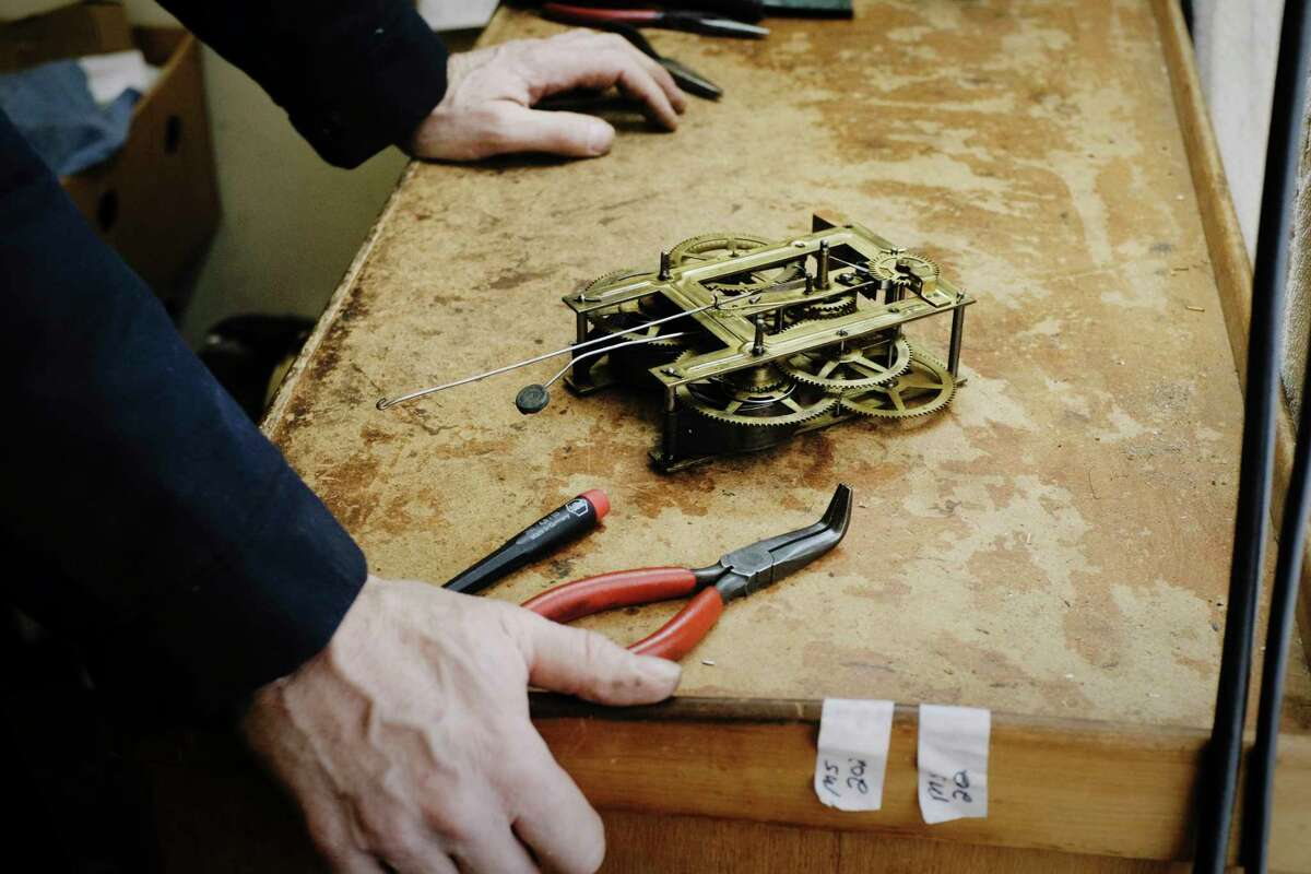James Dunbrook,a freelance horologist at The Clock Works, works on a clock movement he removed from inside a clock on Tuesday, Feb. 23, 2021, in Schenectady, N.Y. (Paul Buckowski/Times Union)