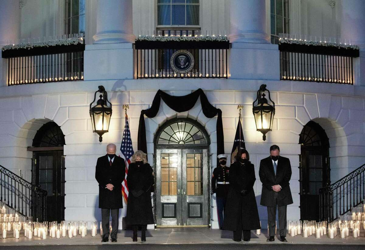 President Joe Biden, first lady Jill Biden, Vice President Kamala Harris and her husband, Doug Emhoff, hold a moment of silence during a candelight ceremony in honor of those who lost their lives to the coronavirus on the South Lawn of the White House in Washington, D.C., on Monday.