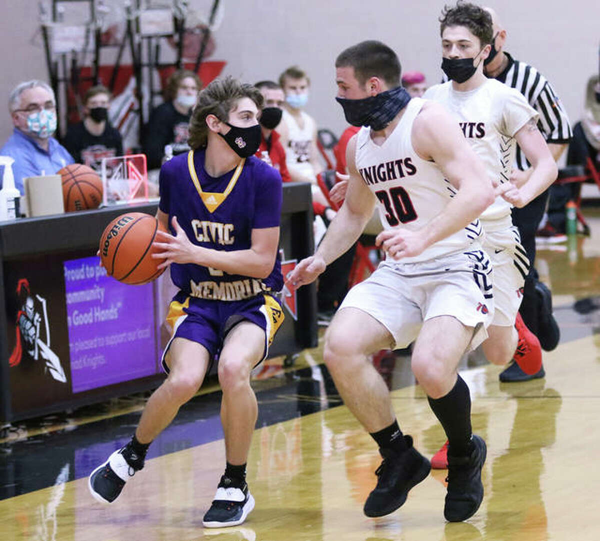 CM's D.J. Dutton (left) pulls up on the break, looking for a teammate while Triad's Sam Yager (30) defends in the second half of their Mississippi Valley Conference boys basketball game Tuesday night at Rich Mason Gym in Troy.