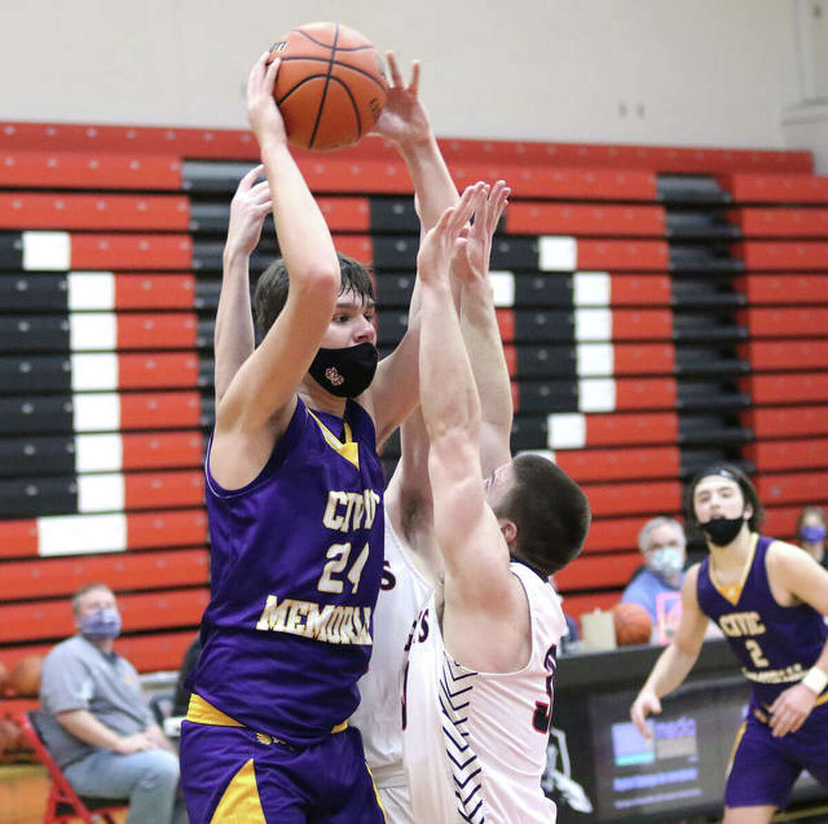 CM's 6-foot-10 sophomore Sam Buckley (left) passes out of a double team by Triad on Tuesday night in Troy.