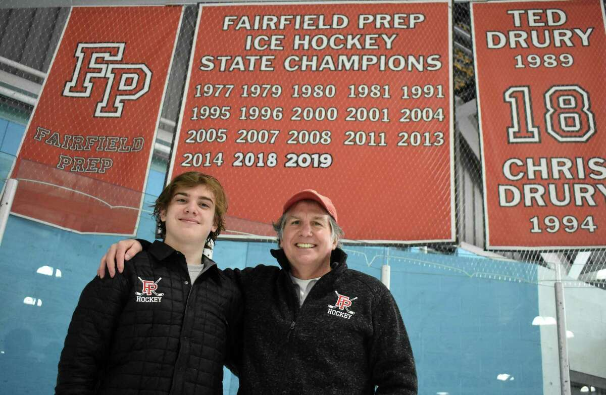 Fairfield Prep senior goalie Tommy Martin poses with his father Kevin Martin, who won three state titles as the Fairfield Prep goalie from 1978-1981, in front of the Fairfield Prep state championship banner at the Wonderland of Ice rink in Bridgeport on Friday, Feb. 19, 2021.