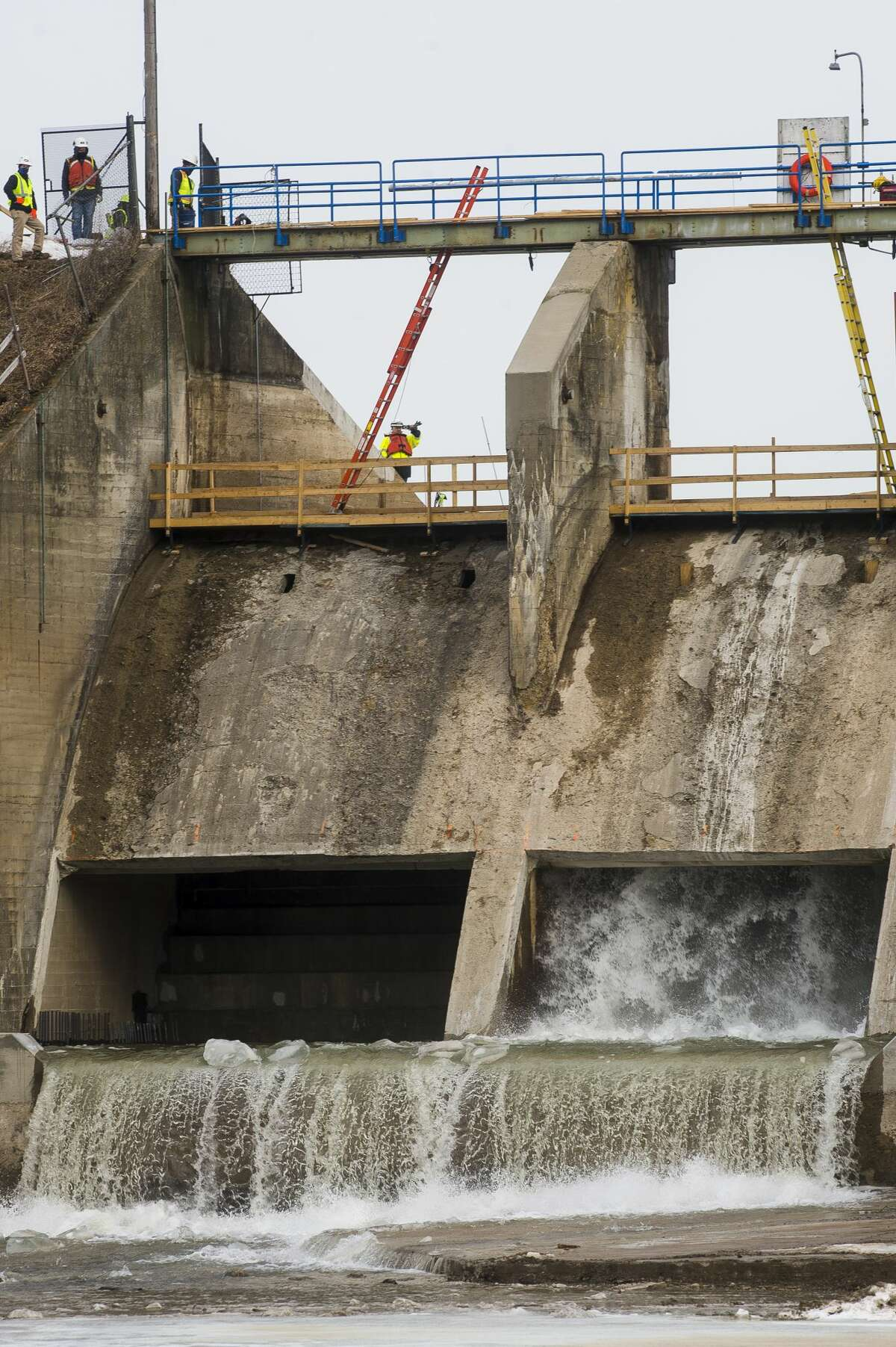 Water begins to trickle through a spillway gate of the Edenville Dam as the drawdown of the Tobacco River spillway begins Wednesday morning, Feb. 24, 2021 in Beaverton. The drawdown is a necessary part of an ongoing project to make the dam more stable and reduce the risk of flash flooding, after the Edenville Dam failed last May. (Katy Kildee/kkildee@mdn.net)