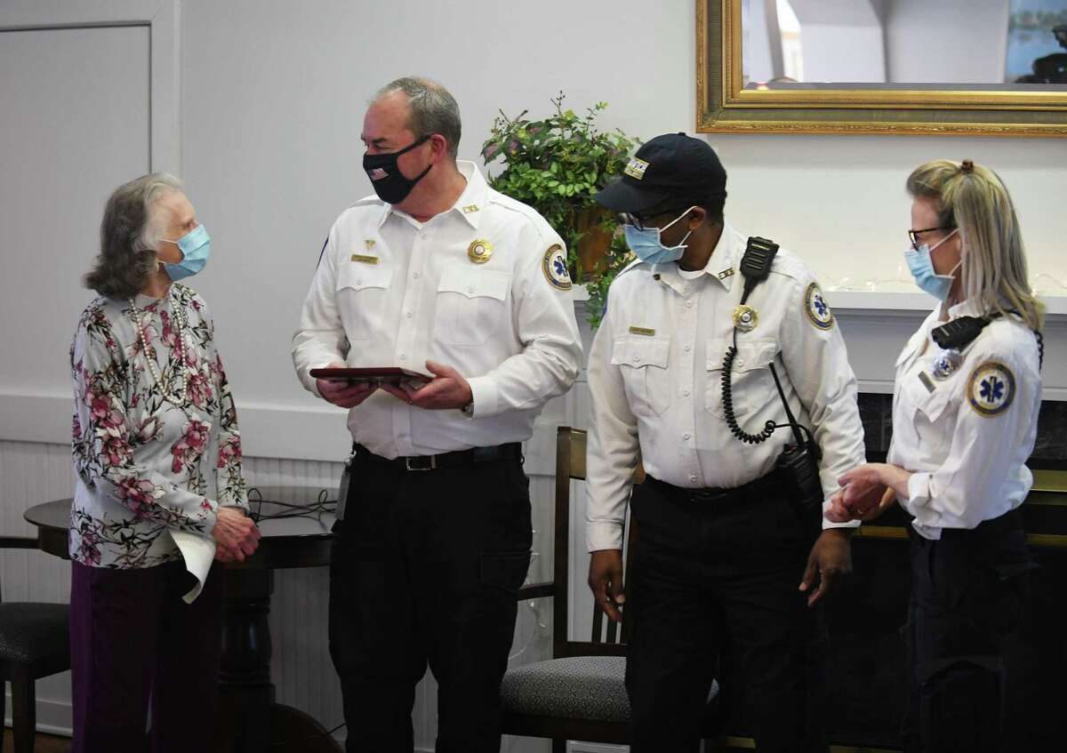 Hill House resident Ann Faragasso presents GEMS first responders Patrick O'Connor, John McRae, and Linette Usowski with a plaque at Hill House in the Riverside section of Greenwich, Conn. Tuesday, Feb. 23, 2021. GEMS first responders were presented with a plaque and thanked by residents during a short ceremony at Hill House Tuesday.