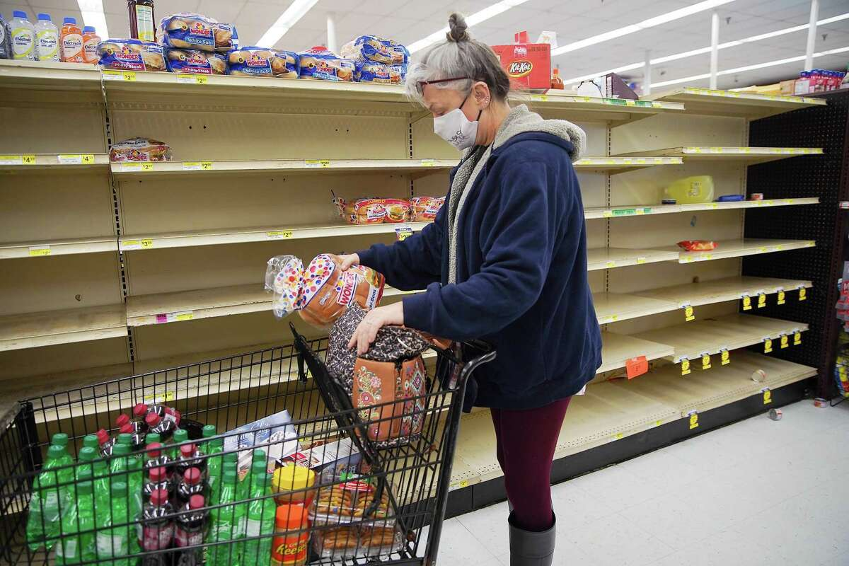 Kathy McClure grabs some bread on a near-empty shelf at Arlen's Market in Galveston on Wednesday, Feb. 17, 2021. McClure has been out of power since Sunday morning.