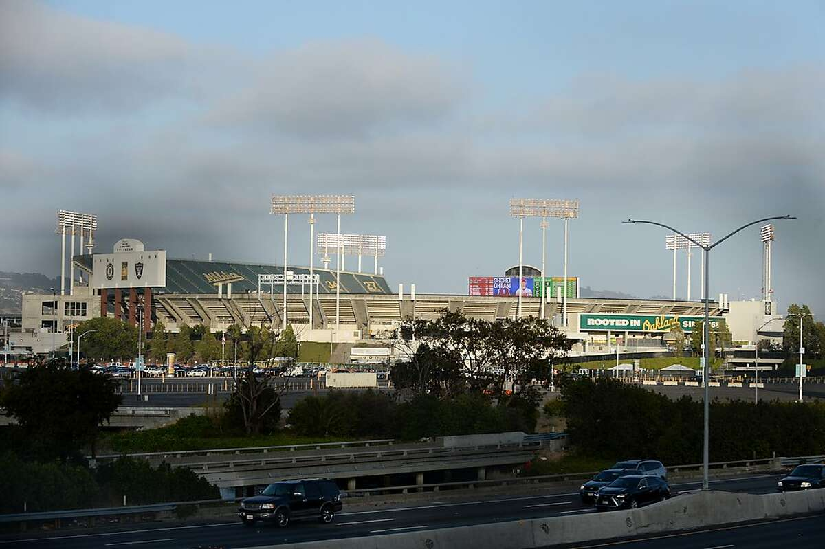 Light traffic whirrs by a quiet Oakland Coliseum stadium on July 24, 2020, during the Oakland A's home opener against the L.A. Angels in Oakland, Calif.
