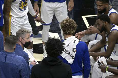 Golden State Warriors head coach Steve Kerr, left, talks to his players during a timeout in the first half of an NBA basketball game against the Orlando Magic, Friday, Feb. 19, 2021, in Orlando, Fla. (AP Photo/Phelan M. Ebenhack)