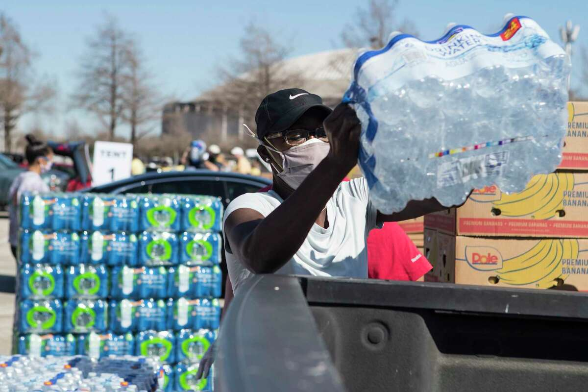 Eunice Russ places a case of water into the back of a truck during a Neighborhood Super Site food distribution by the Houston Food Bank at NRG Stadium Tuesday, Feb. 23, 2021 in Houston. Houston Food Bank volunteers distributed food to several thousand Houstonians in need following the severe winter storm that knocked power and water out throughout the area.