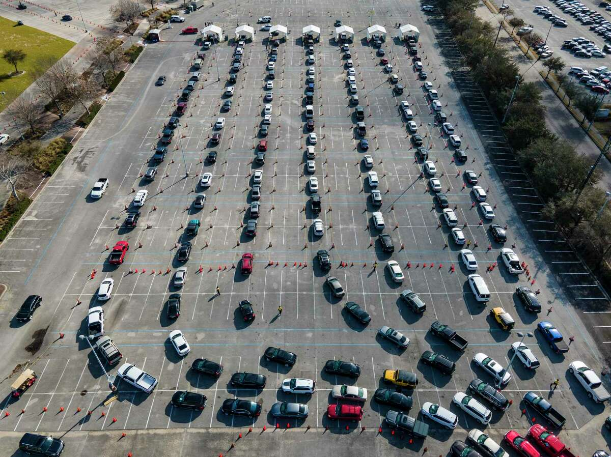 Cars line up in a parking lot at NRG Park as people wait to receive a vaccine to protect them from COVID-19 at a federally supported supersite at the Harris County facility, Wednesday, Feb. 24, 2021, in Houston.