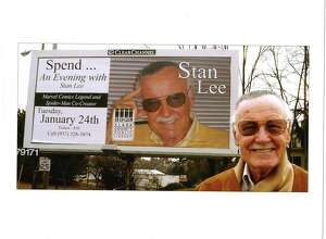 Stan Lee poses in front of a billboard promoting an upcoming appearance.