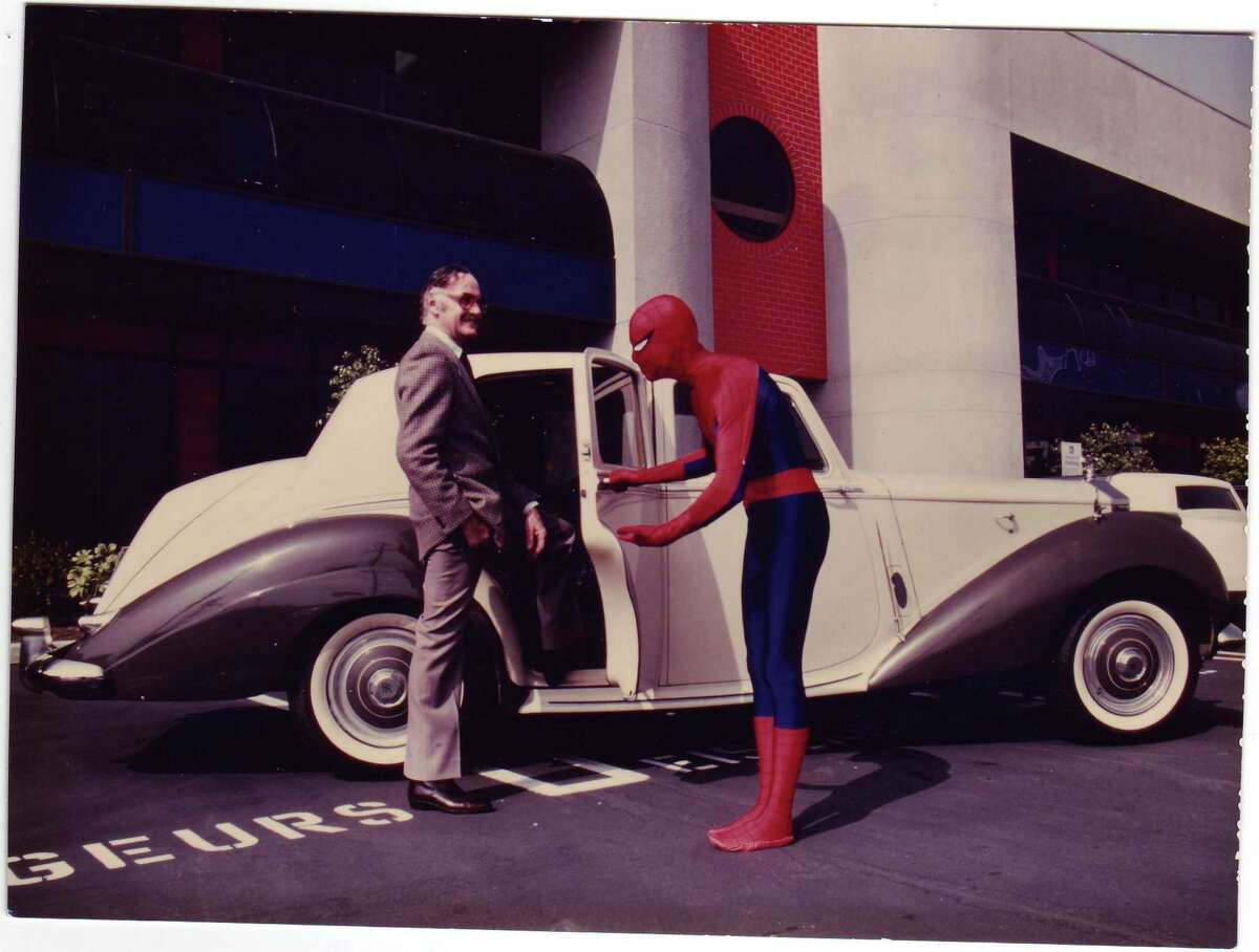 In the early 1980s, Stan Lee is greeted at his personal Rolls-Royce by a Marvel employee in a Spider-Man costume.