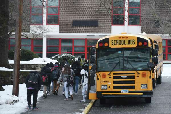 Students enter Turn of River Middle School in Stamford, Conn. Tuesday, Feb. 23, 2021.