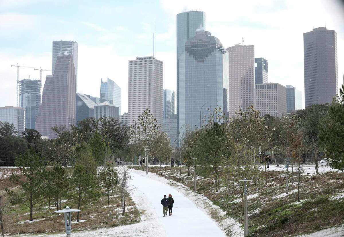 Two people walk through snow as a winter storm hits Houston on Monday, Feb. 15, 2021, at Buffalo Bayou Park in Houston.