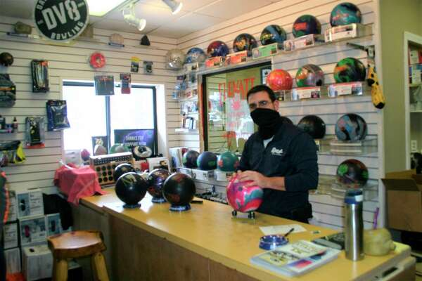 Elevate, the Bowler's Shop, owner David Nawrot restocks his shelves with help form a $5,000 MEDC Small Business Survival Grant award. The shop is now open regular hours with COVID-19 restrictions in place. (Pioneer photo/Cathie Crew)