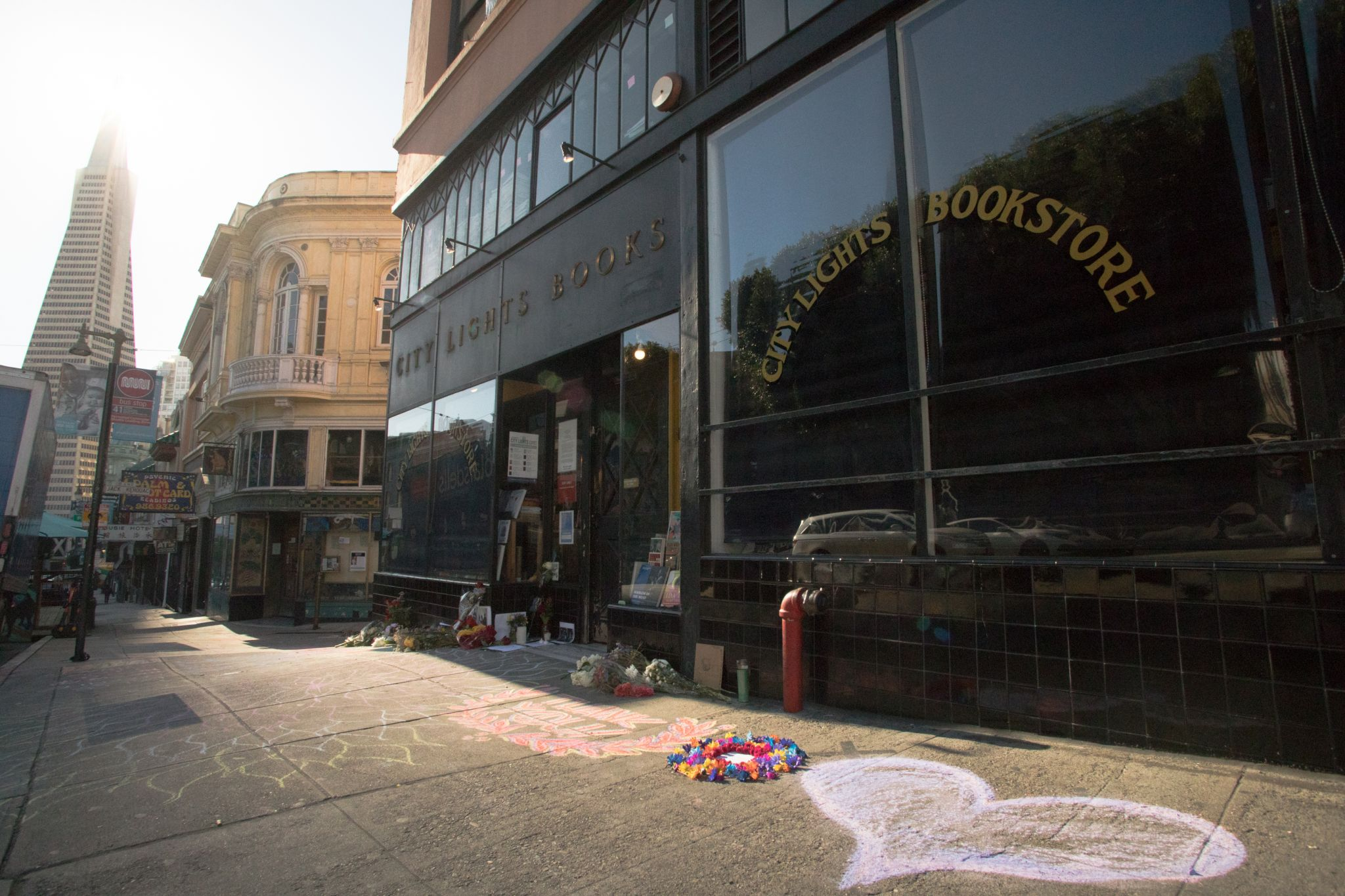 Chalk art covers the sidewalk in front of City Lights bookstore in North Beach. An impromptu memorial in honor of Lawrence Ferlinghetti appeared overnight in front of the City Lights bookstore in San Francisco on Feb. 24, 2021.