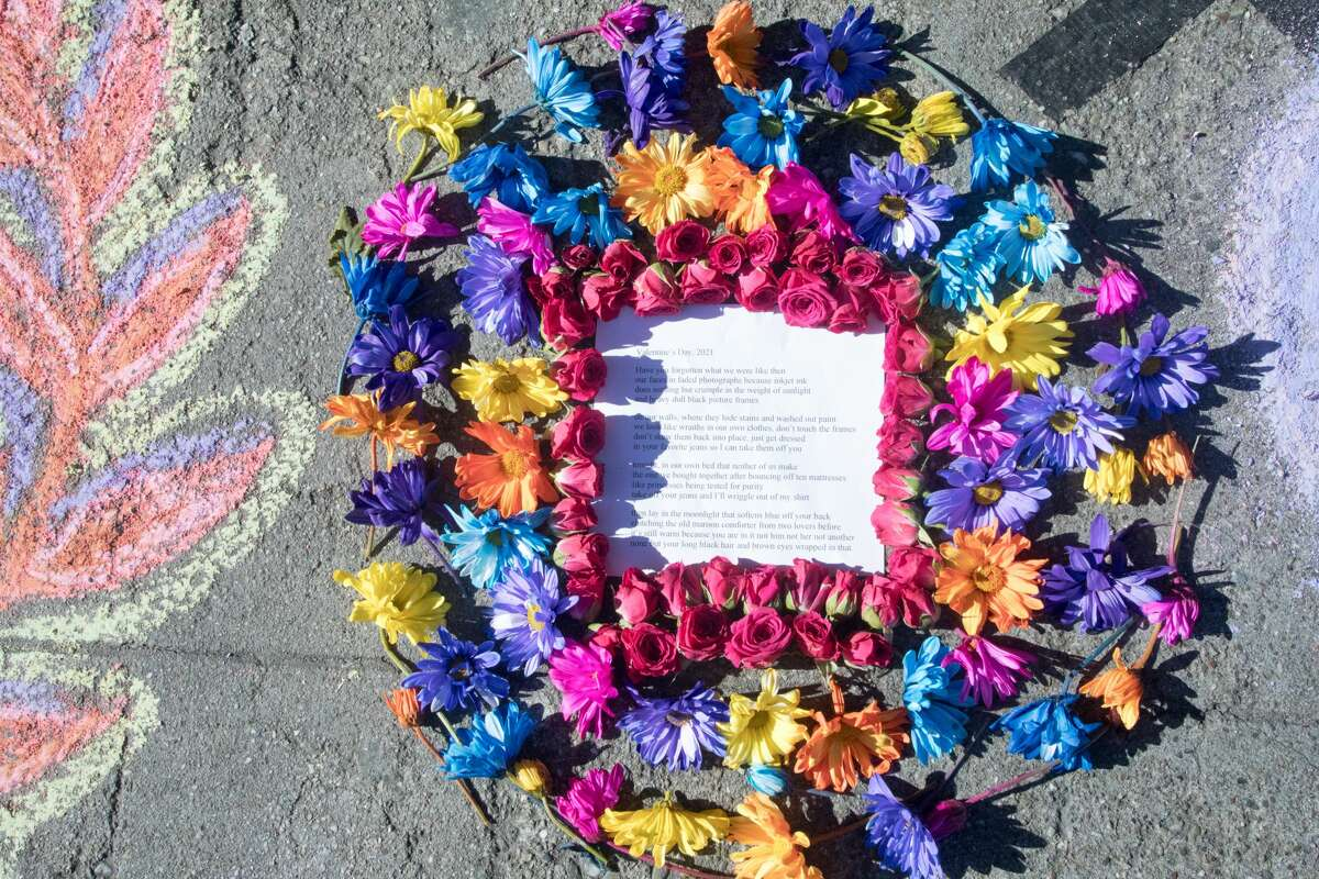A poem surrounded by flowers is part of an impromptu memorial in honor of Lawrence Ferlinghetti that appeared overnight in front of City Lights Booksellers & Publishers in San Francisco on Feb. 24, 2021.