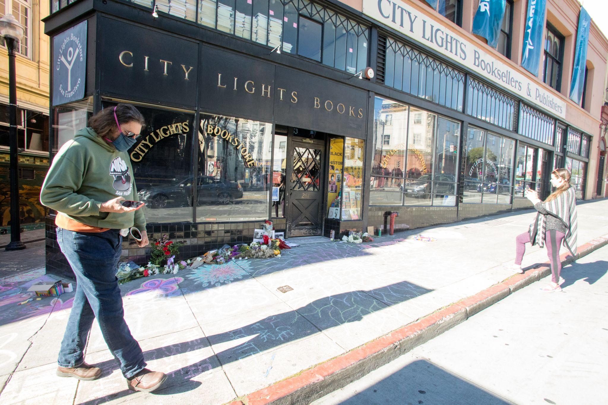 Visitors look at the chalk art covering the sidewalk in front of City Lights bookstore in North Beach. An impromptu memorial in honor of Lawrence Ferlinghetti appeared overnight in front of the City Lights bookstore in San Francisco on Feb. 24, 2021.