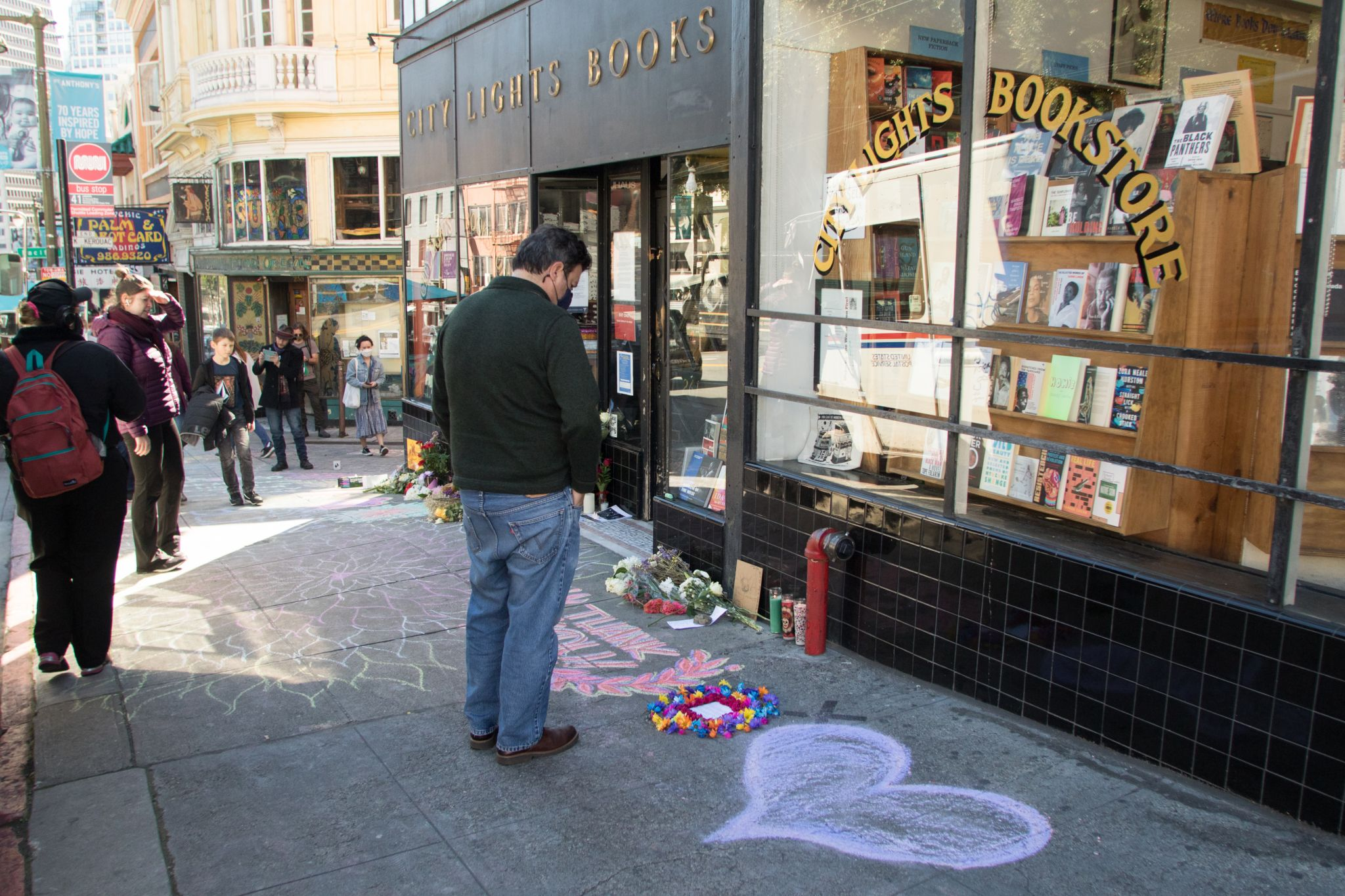 A group of people view an impromptu memorial in honor of Lawrence Ferlinghetti that appeared overnight in front of City Lights Booksellers & Publishers in San Francisco on Feb. 24, 2021.