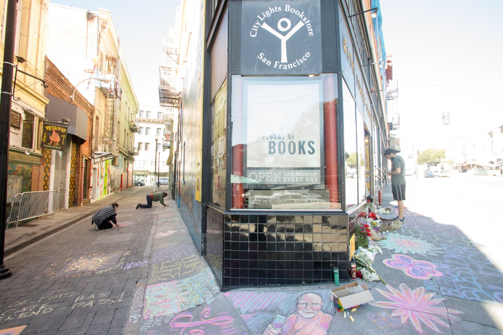 Several people add to the chalk art memorial outside City Lights Booksellers & Publishers. An impromptu memorial in honor of Lawrence Ferlinghetti appeared overnight in front of the City Lights bookstore in San Francisco on Feb. 24, 2021.