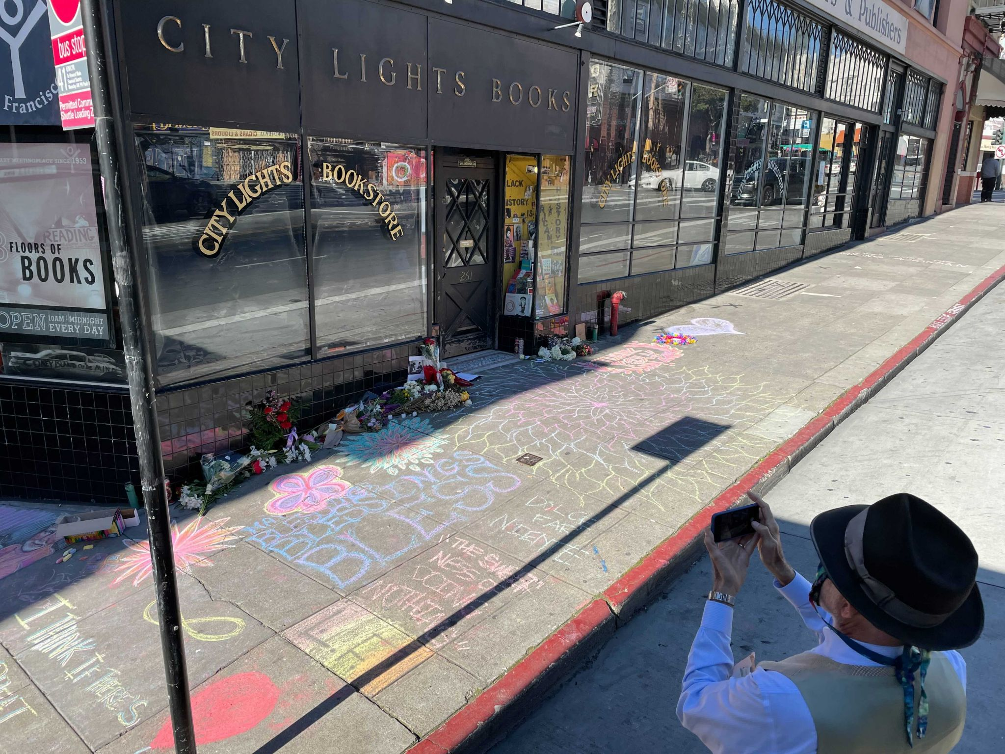 A visitor takes photos of an impromptu memorial in honor of Lawrence Ferlinghetti that appeared overnight in front of City Lights Booksellers & Publishers in San Francisco on Feb. 24, 2021.