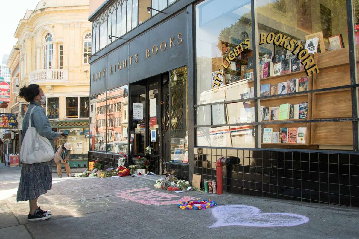 A passerby views an impromptu memorial in honor of Lawrence Ferlinghetti that appeared overnight in front of the City Lights bookstore in San Francisco on Feb. 24, 2021.