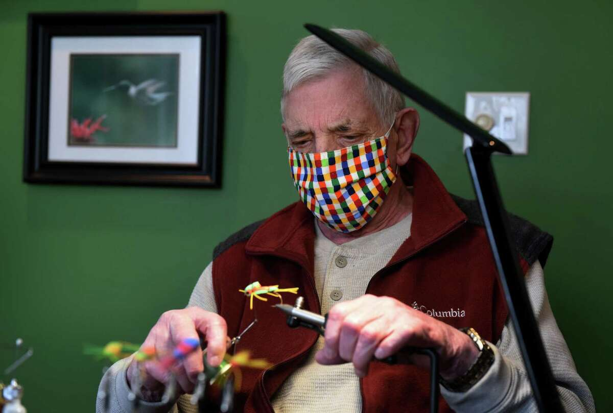 Richard Atkinson, of Clearwater Trout Unlimited and Capital District Fly Fishers, ties a fly he makes for catching bass on Wednesday, Feb. 24, 2021, at his home in Niskayuna, N.Y. (Will Waldron/Times Union)
