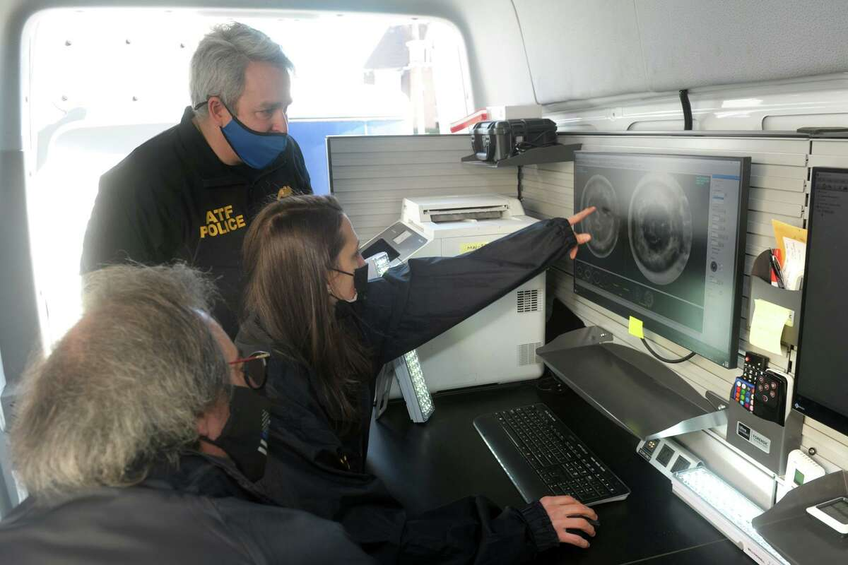 Rachel Beninati of the Connecticut State Police forensics lab, seated center, looks at high resolution scans of a bullet casings during a demonstration inside the ATF's National Integrated Ballistic Information Network (NIBIN) mobile van in Bridgeport, Conn. Feb. 24, 2021. The van will be available to the Bridgeport Police Department for the thirty-day training period. Beninati is seen here with the ATF's John Hayes, standing, and Bridgeport police detective Paul Nikola.