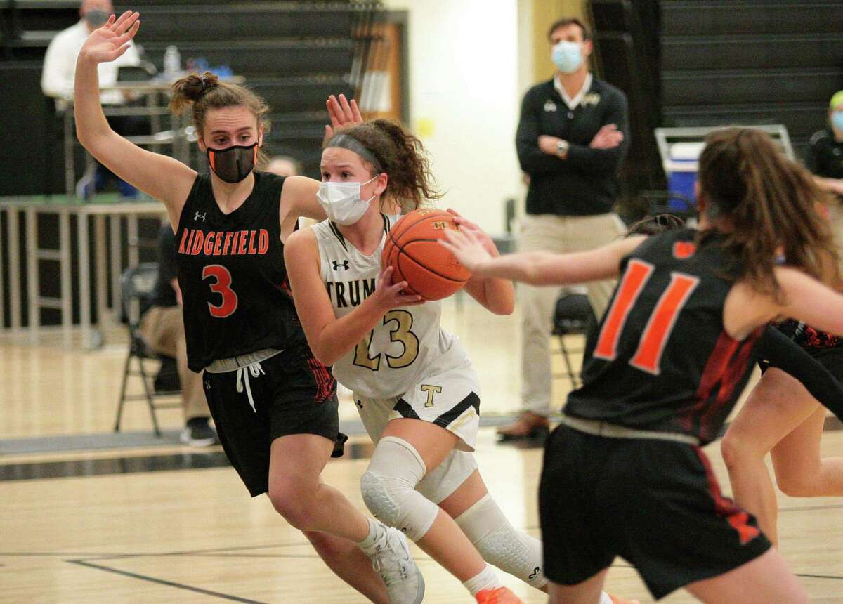 Trumbull's Grace Lesko (23) drives the ball to the basket between Ridgefied's Kelly Chittenden (3), left, and Harley Zins (11) during girls basketball action in Trumbull, Conn., on Wednesday Feb.10, 2021.