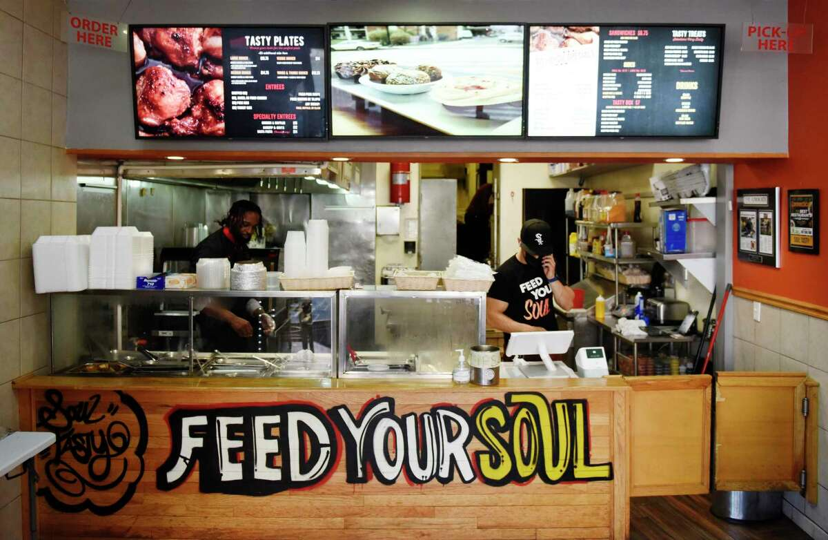 Co-owners Jean Gabriel, left, and Will Reyes work at Soul Tasty in Stamford on Wednesday.