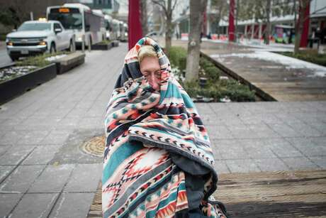 Michelle DeFord, 52, bundles up in a blanket to stay warm outside the warming shelter at the George R. Brown Convention Center, where she is staying during the frigid cold weather Tuesday, Feb. 16, 2021 in Houston. Temperatures stayed below freezing Tuesday, with many still without power.