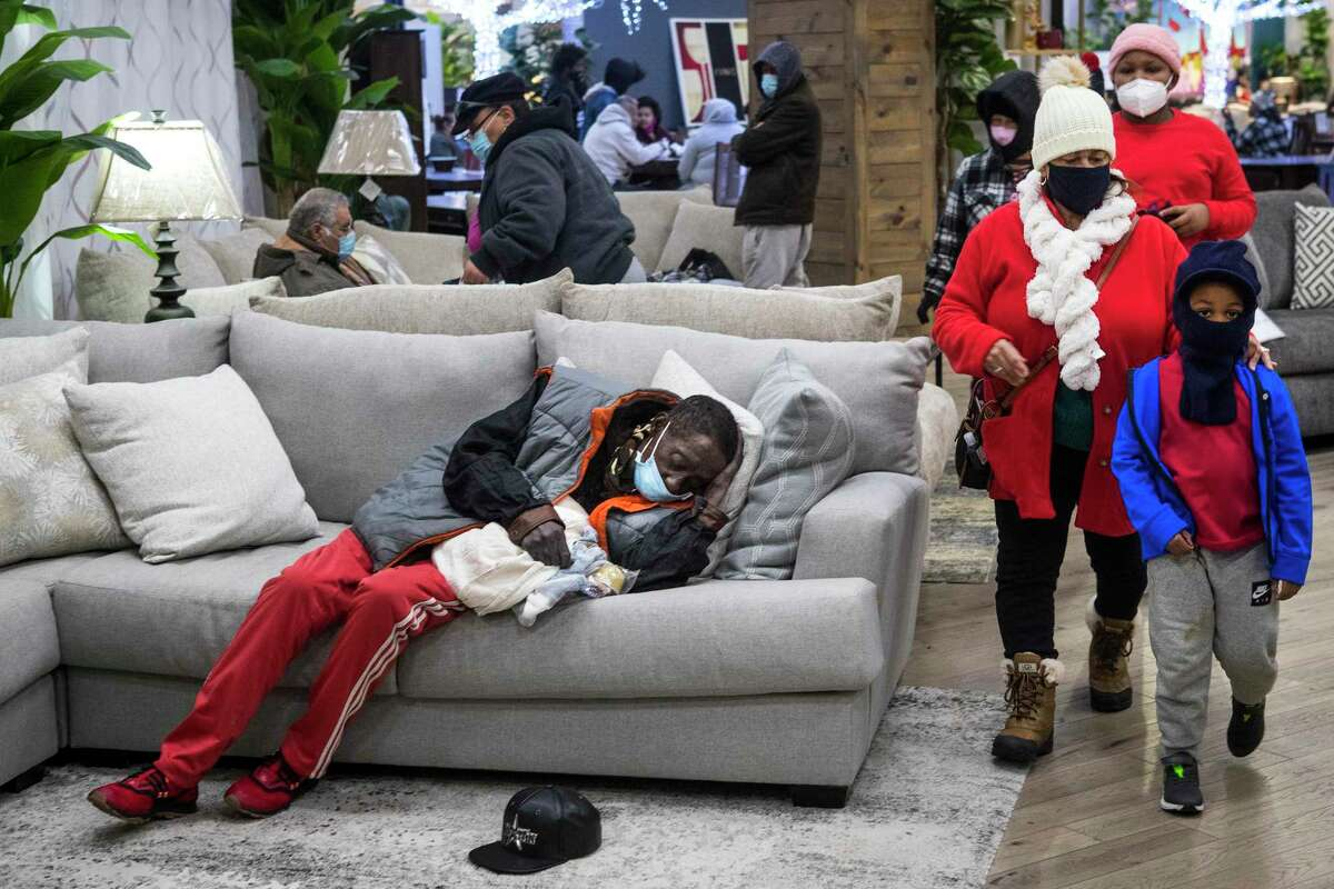 """People gather at a warming shelter set up at Gallery Furniture Tuesday, Feb. 16, 2021 in Houston. As emperatures stayed below freezing Tuesday, and many in the neighborhood around the furniture store without power, Jim """"Mattress Mack"""" McIngvale opened his store to help area residents come in from the cold."""