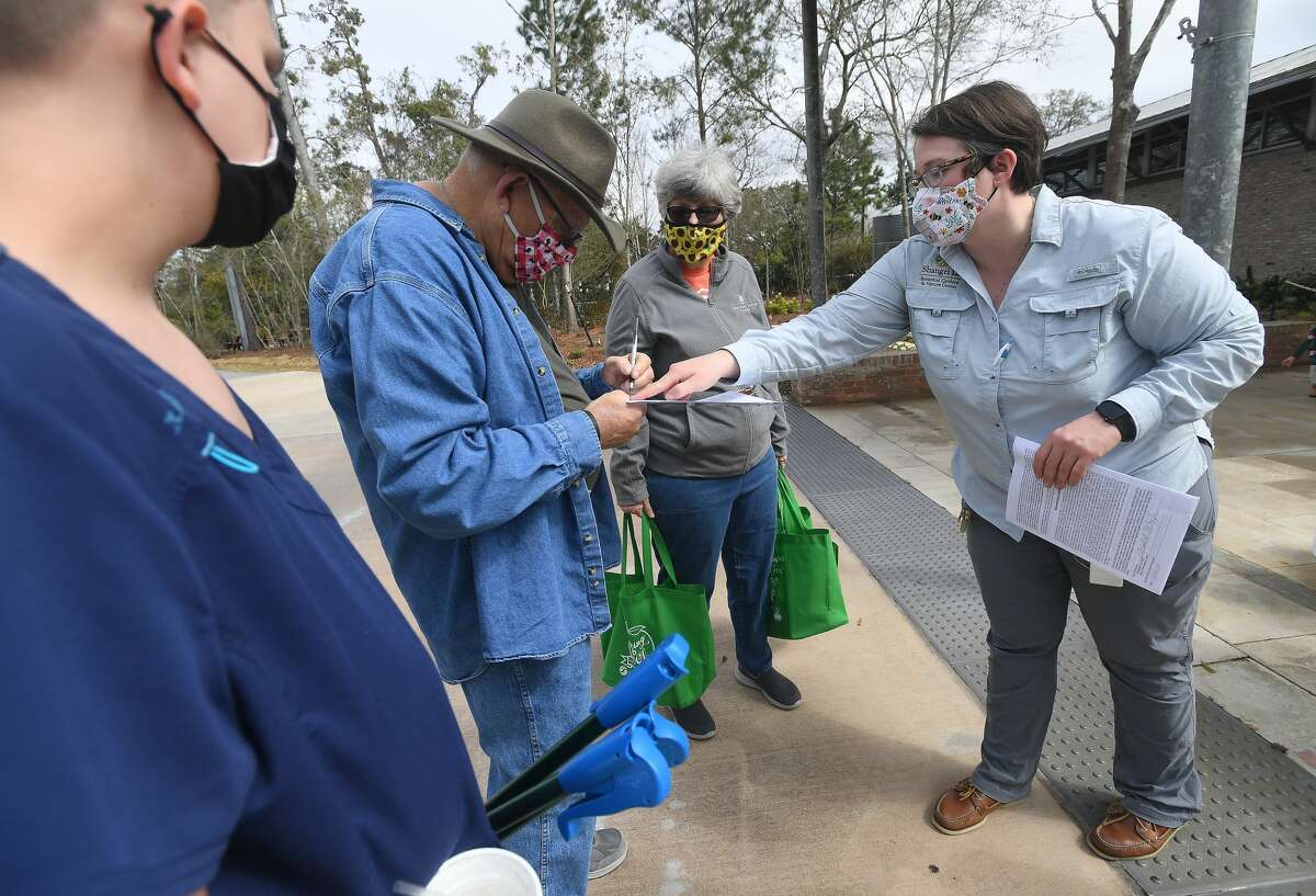 Shangri La's Katie Krantz registers Mary and Frank McCoy and their grandson Kade McLemore for Saturday's 26th annual Community Trash Off in Orange. The family signed up to join in the trash pick-up day after visiting the gardens Wednesday. Residents are encouraged to join in, cleaning up litter wherever they see fit, and are supplied with a work vest, gloves, trash bags, bottled water and a grabber tool. The annual event is sponsored by Shangri La in conjunction with the City of Orange. Trash bag pick-up is available for those without means to haul it to the boat ramp dumpster site. Photo made Wednesday, February 24, 2021 Kim Brent/The Enterprise