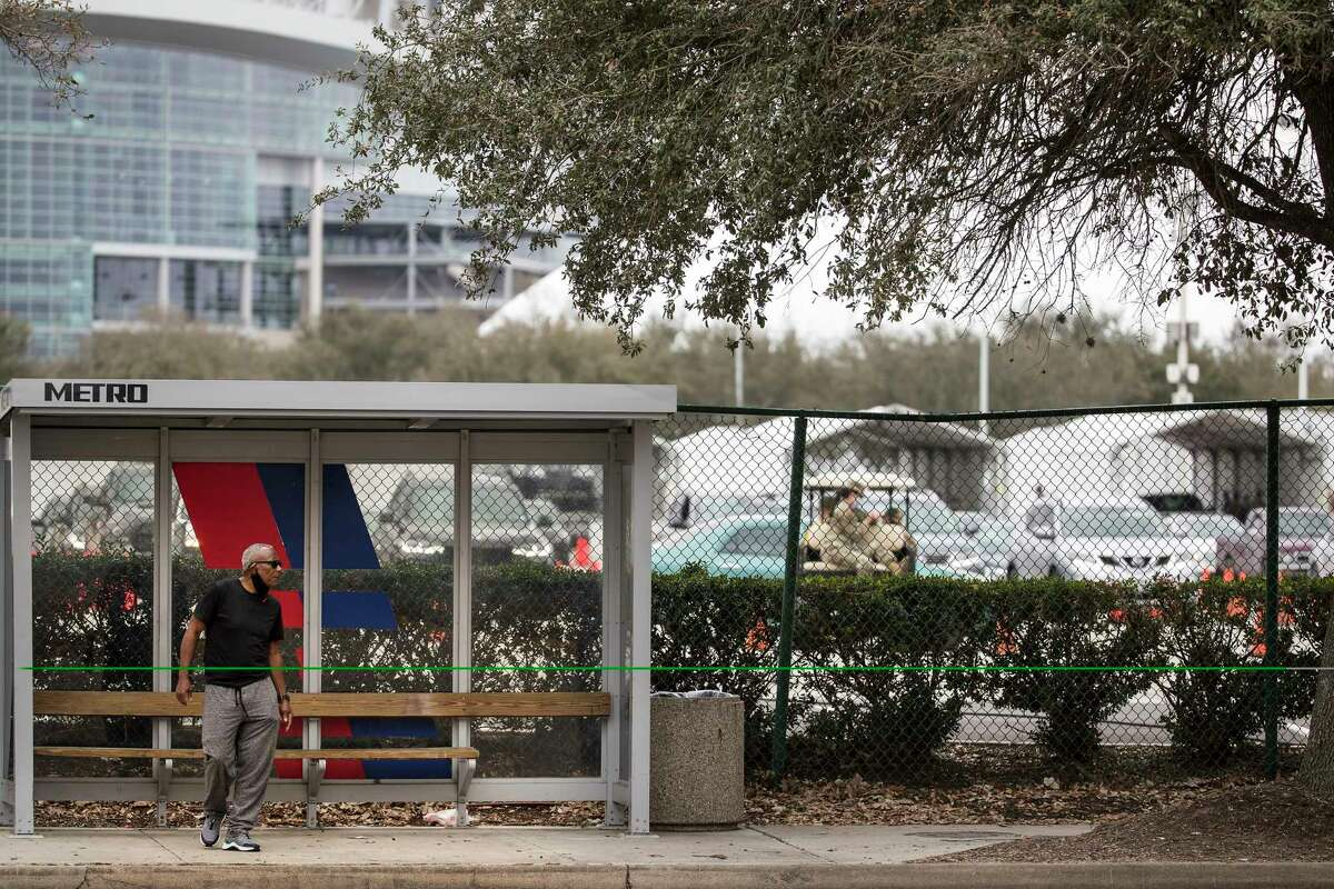 A man waits at a bus stop along Main Street next to the a Federal Emergency Management Agency COVID-19 vaccination super site at NRG Park Wednesday, Feb. 24, 2021 in Houston. Despite being one of the most transit-friendly locations in the region with access to light rail and bus service, walk-ups are not part of the plan presently at the site that opened Wednesday in coordination with the FEMA.
