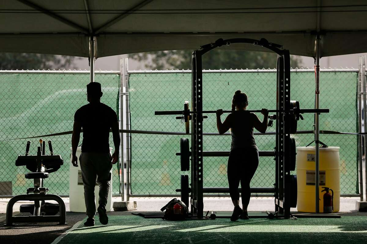 Michelle Espland (right) exercises in the outdoor tent at 24 Hour Fitness in Walnut Creek, California on Wednesday, Dec. 16, 2020.