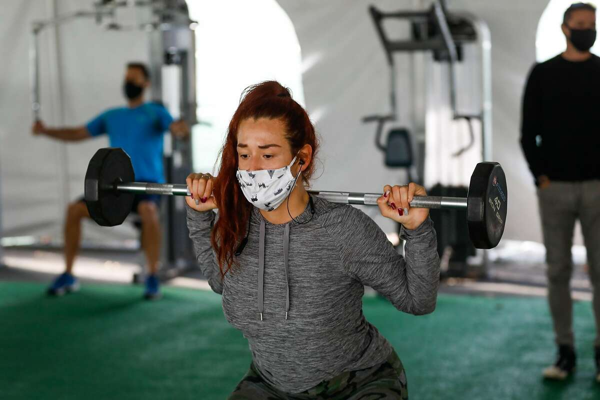 Jocelyne Garcia exercises in the outdoor tent at 24 Hour Fitness in Walnut Creek, California on Wednesday, Dec. 16, 2020.