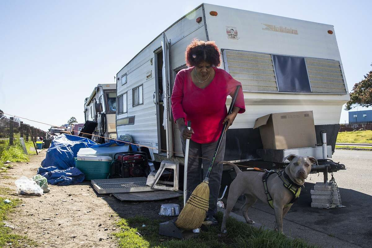 Amilee Smith, 60, cleans up the area outside of her RV with her dog Mimi while parked at an RV encampment along Rydin Road in Richmond, Calif. Monday, February 22, 2021.