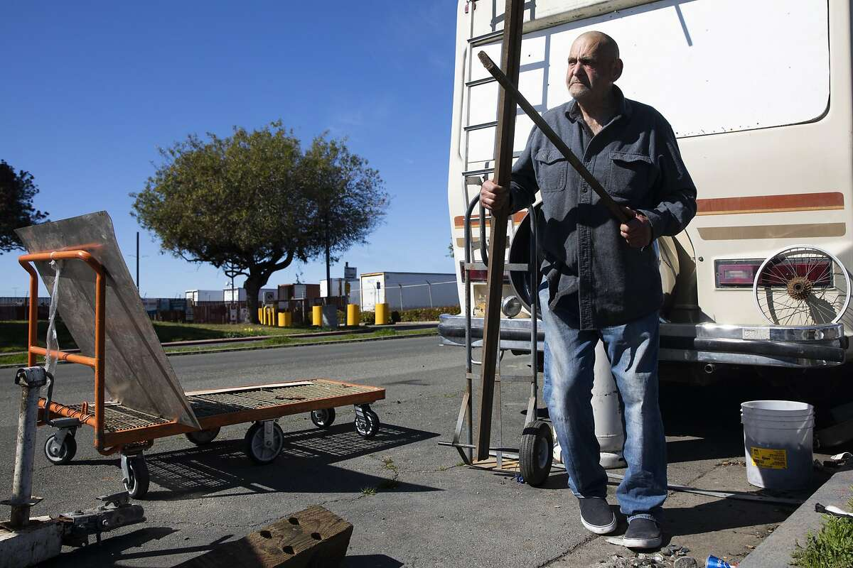 Jim Hauso, 71, works to clean up the area outside of his RV while parked at an RV encampment along Rydin Road in Richmond, Calif. Monday, February 22, 2021. Richmond city officials are pursuing opening an RV site for at least 30 people to reside. A plan for 100 people at a nearly empty mall was shot down.