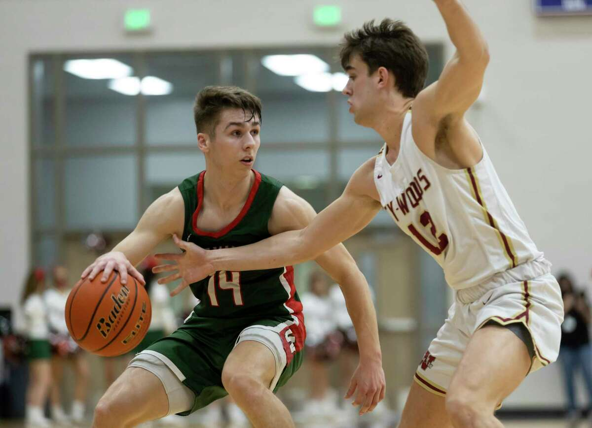 The Woodlands guard Isaiah Brown (14) dribbles the ball while under pressure from Cypress Woods guard Charles Haubein (12) during the second quarter of a Region II-6A area round boys basketball game at Klein Cain High School, Wednesday, Feb. 24, 2021, in Spring.