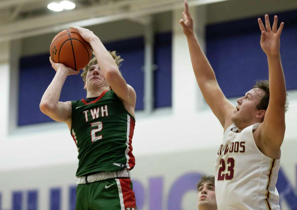 The Woodlands guard Shey Eberwein (2) shoots for the basket despite pressure from Cypress Woods forward Dylan Cormier (23) during the second quarter of a Region II-6A area round boys basketball game at Klein Cain High School, Wednesday, Feb. 24, 2021, in Spring.