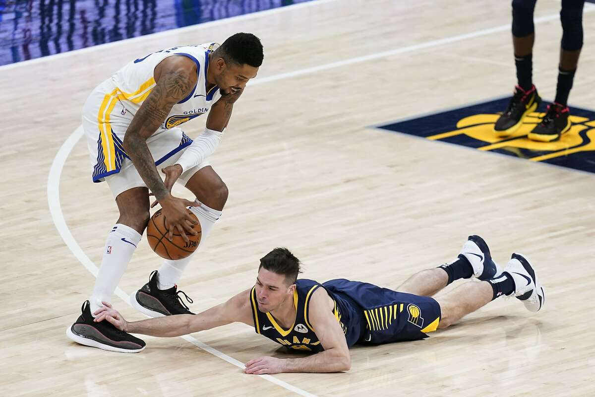 Indiana Pacers' T.J. McConnell (9) dives for a loose ball against Golden State Warriors' Kent Bazemore during the first half of an NBA basketball game Wednesday, Feb. 24, 2021, in Indianapolis. (AP Photo/Darron Cummings)