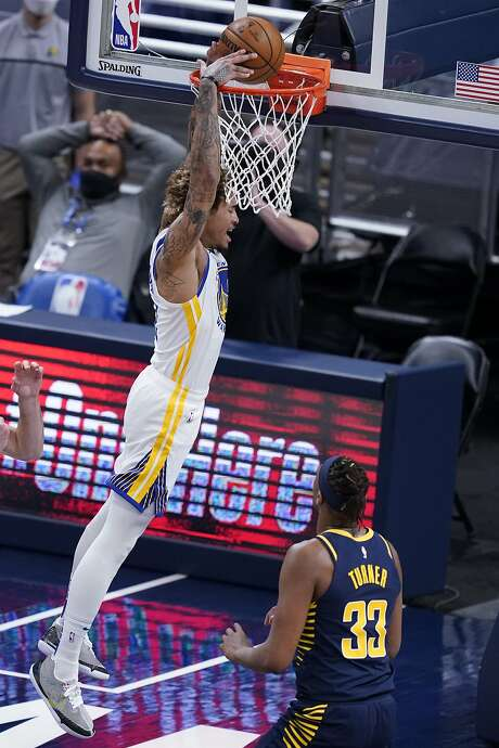 Golden State Warriors' Kelly Oubre Jr. (12) dunks next to Indiana Pacers' Myles Turner (33) during the first half of an NBA basketball game Wednesday, Feb. 24, 2021, in Indianapolis. (AP Photo/Darron Cummings)