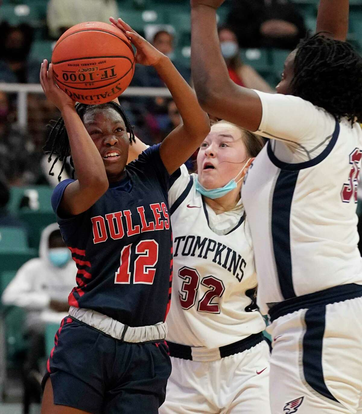Dulles Nya Jakiya Thompson (12) looks to shoot around Tompkins Macy Spencer (32) and Fiyin Adeleye (35) during girls basketball playoff game at the Merrell Center Wednesday, Feb. 24, 2021 in Katy.