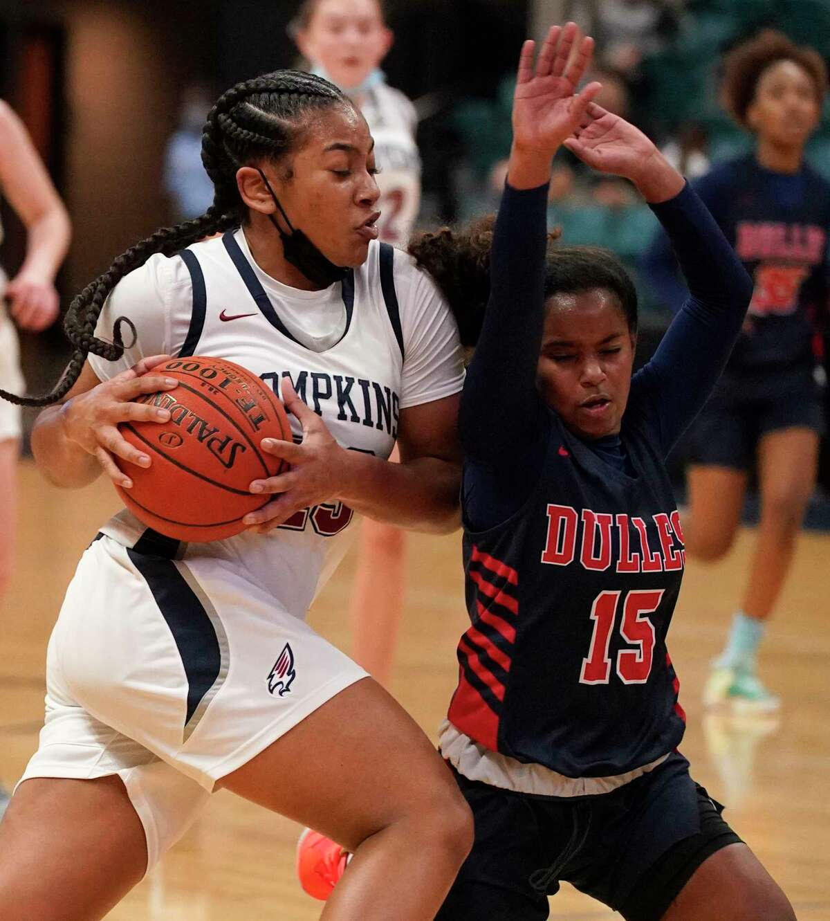 Tompkins Loghan Johnson (23) is fouled by Dulles Victoria Moore (15) during girls basketball playoff game at the Merrell Center Wednesday, Feb. 24, 2021 in Katy.