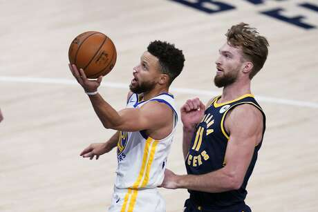 Golden State Warriors' Stephen Curry (30) goes to the basket against Indiana Pacers' Domantas Sabonis during the second half of an NBA basketball game Wednesday, Feb. 24, 2021, in Indianapolis. (AP Photo/Darron Cummings)